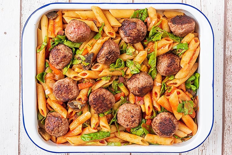 A large rectangular baking dish containing cooked pasta and chopped vegetables all in a tomato sauce. Meatballs have been placed on top
