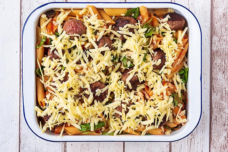 A large rectangular baking dish containing cooked pasta and chopped vegetables all in a tomato sauce. Meatballs have been added and grated cheese sprinkled over everything