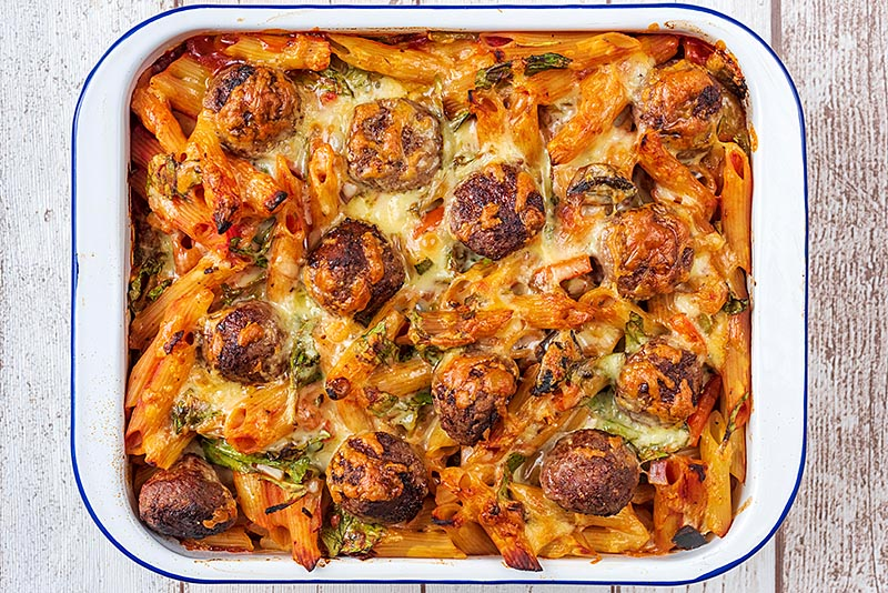 Meatball pasta bake, fresh from the oven with melted cheese covering the top