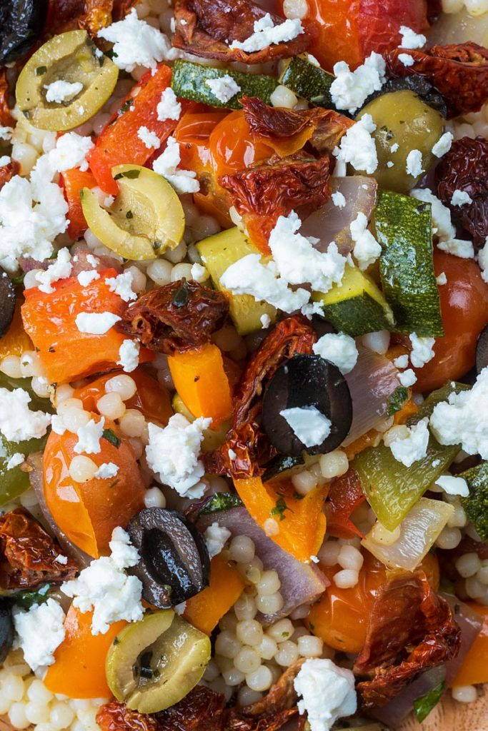 Olives and feta cheese on top of giant couscous salad with roasted vegetables