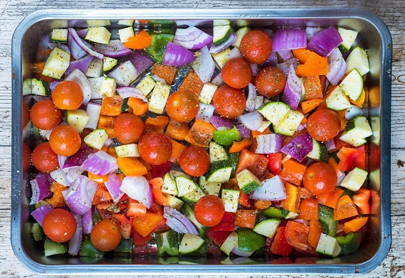 A large roasting tin with chopped vegetables