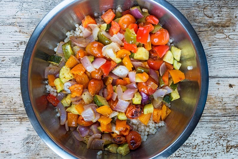 A large mixing bowl containing giant couscous and roasted vegetables