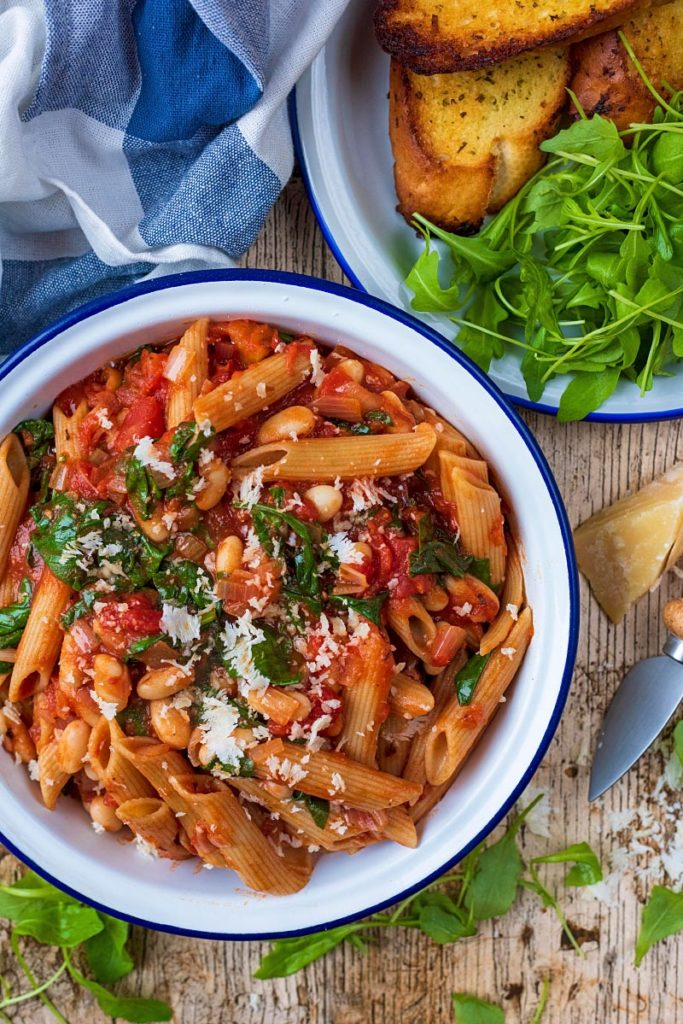White Bean Pasta in a round white dish next to a plate of salad and garlic bread