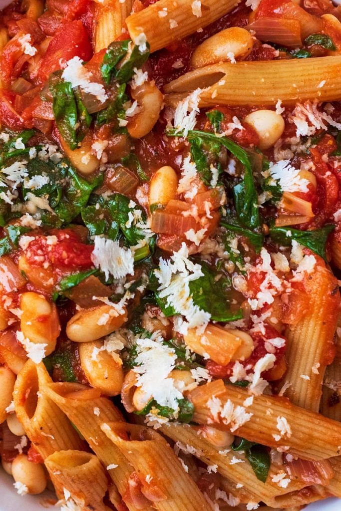 Cooked penne pasta with beans in a tomato sauce topped with parmesan and chopped herbs
