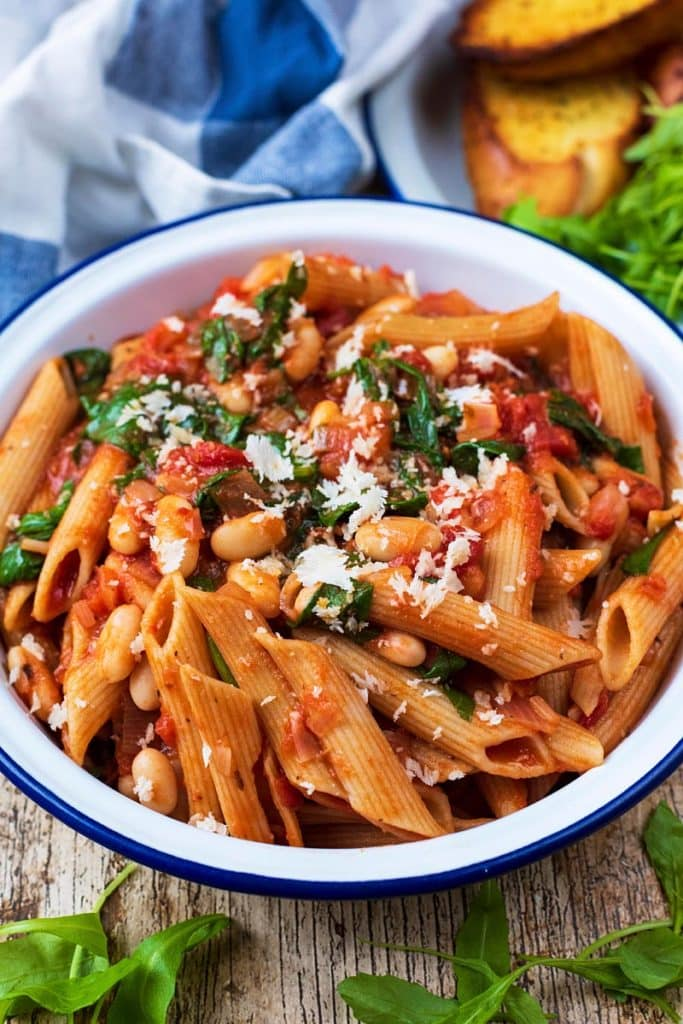 A bowl of pasta in a tomato sauce with beans and herbs