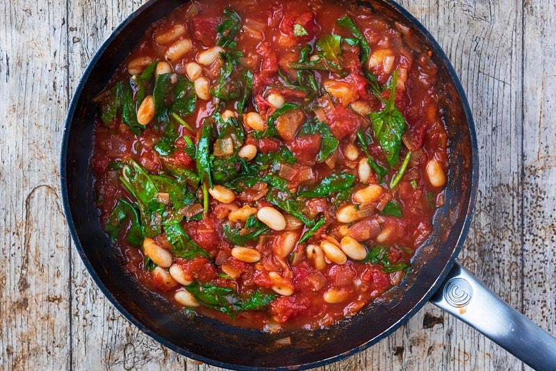 Pasta and beans in a frying pan in a tomato sauce with spinach