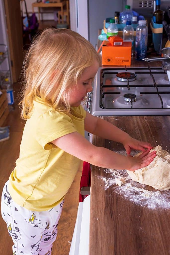 A toddler stood at a work surface kneading dough