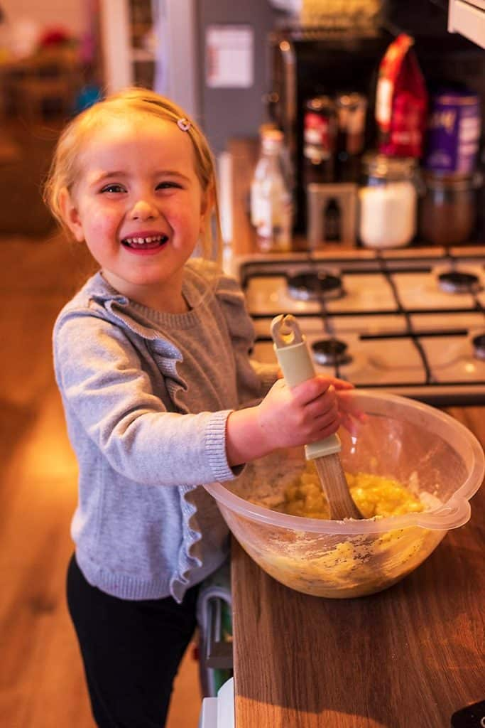A toddler stood at a work surface using a wooden spoon in a mixing bowl