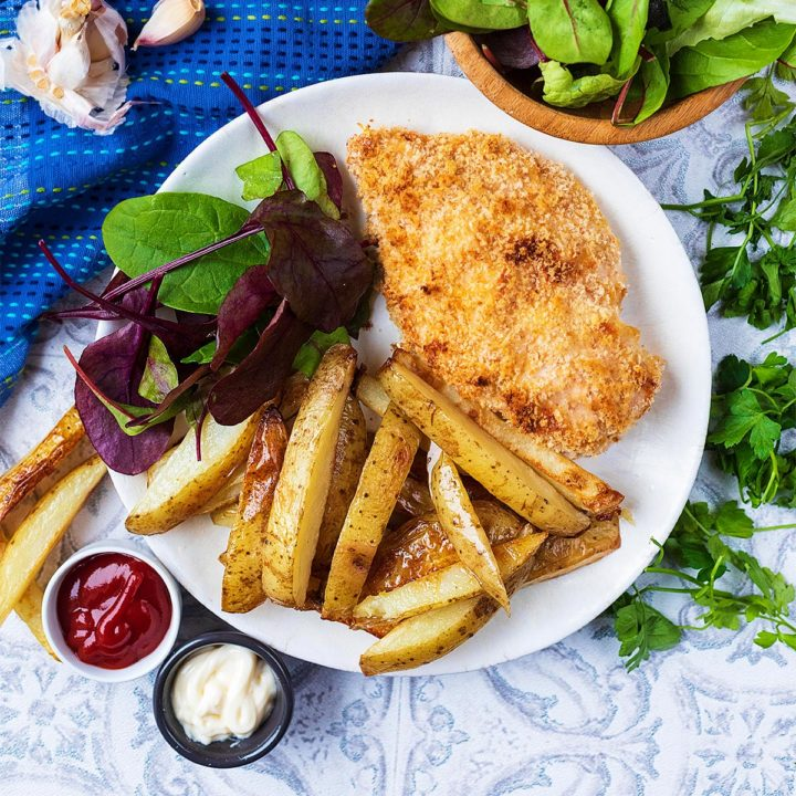 A chicken Kiev on a plate with salad and fries
