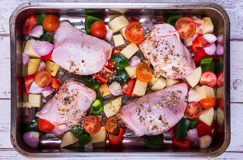 A large baking tin with chicken thighs and vegetables covered in a herby dressing