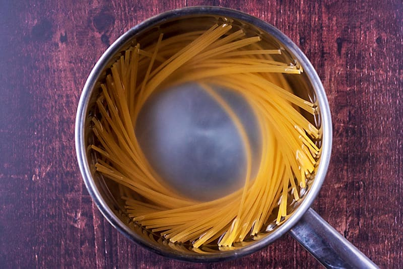 A saucepan with linguine cooking in it