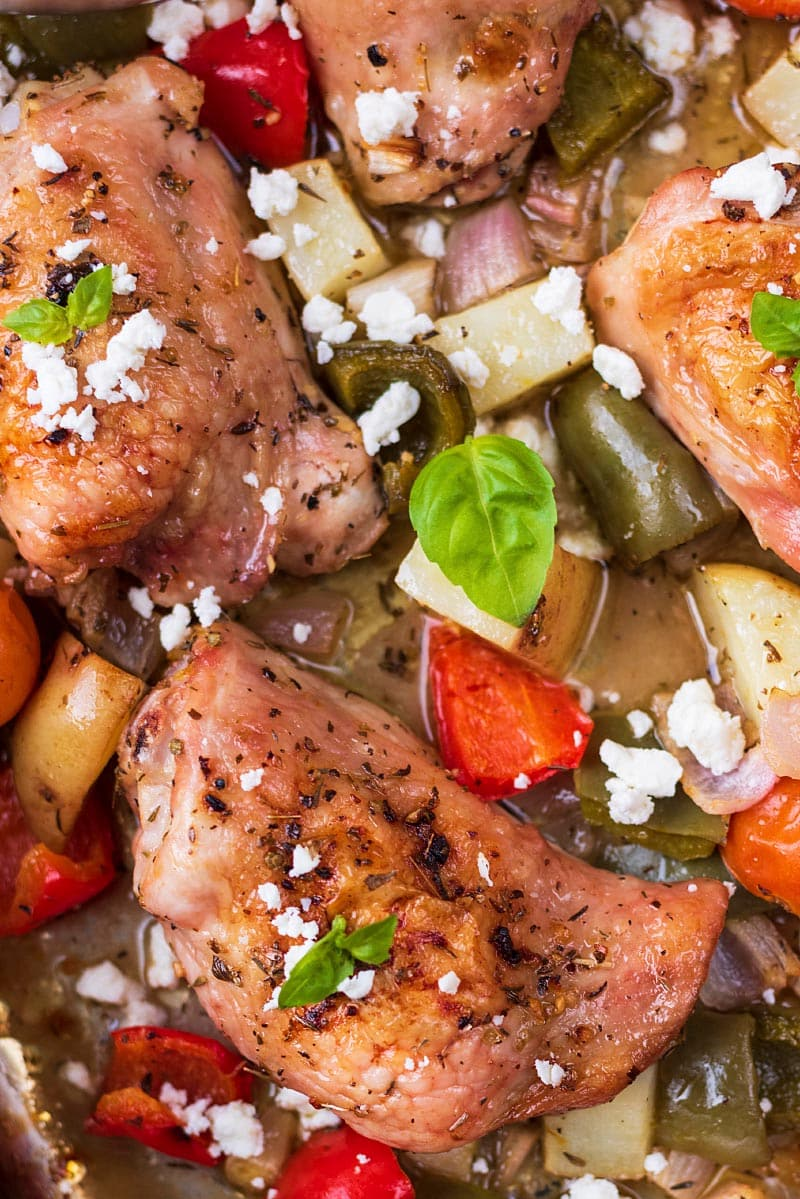 Baked chicken thighs in a sheetpan with chunks of vegetables