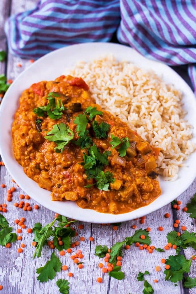 Curry and rice in a bowl with red lentils scattered around