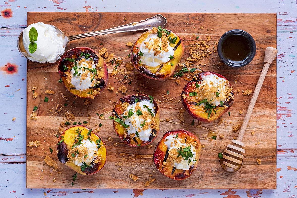 A wooden board with grilled peaches, honey and a spoonful of ice cream