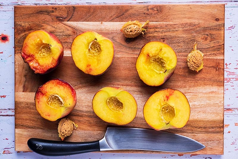 A wooden chopping board with three peaches cut in half. A large chef's knife sits on the board too