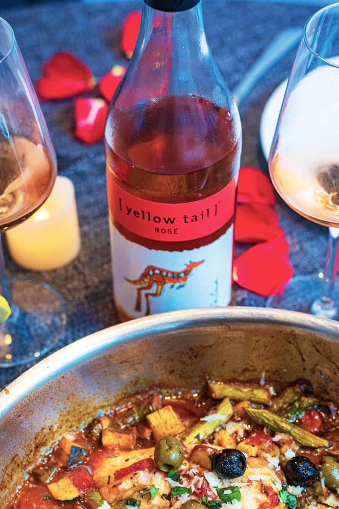 A bottle of Yellow Tail rosé wine next to a pan of chicken and vegetables