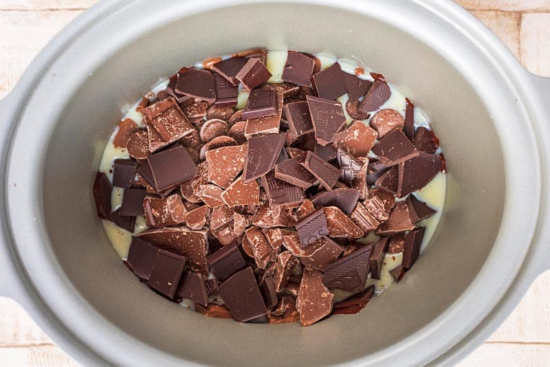 A slow cooker pot full of condensed milk and broken chocolate