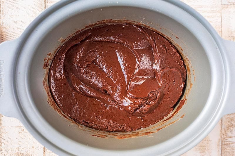 A slow cooker pot containing melted chocolate