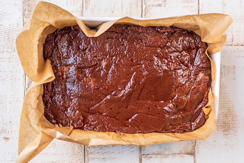 A lined baking dish containing unset fudge mixture