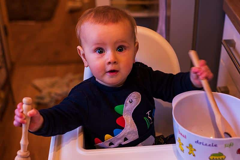 A baby sat in a high chair with a mixing bowl and wooden spoon