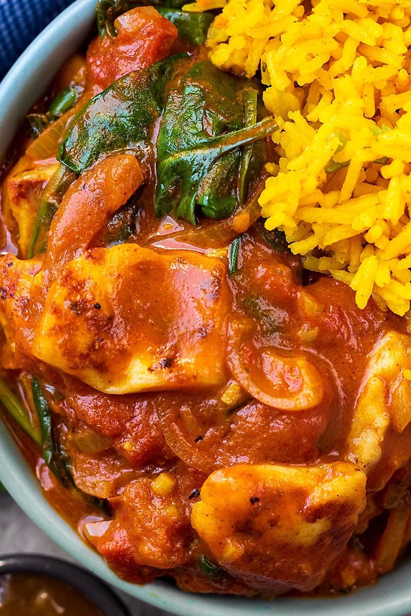 A rich red curry sauce with halloumi and spinach next to some yellow rice