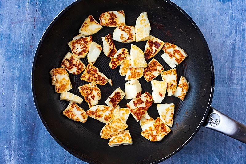 Slices of halloumi cooking in a frying pan