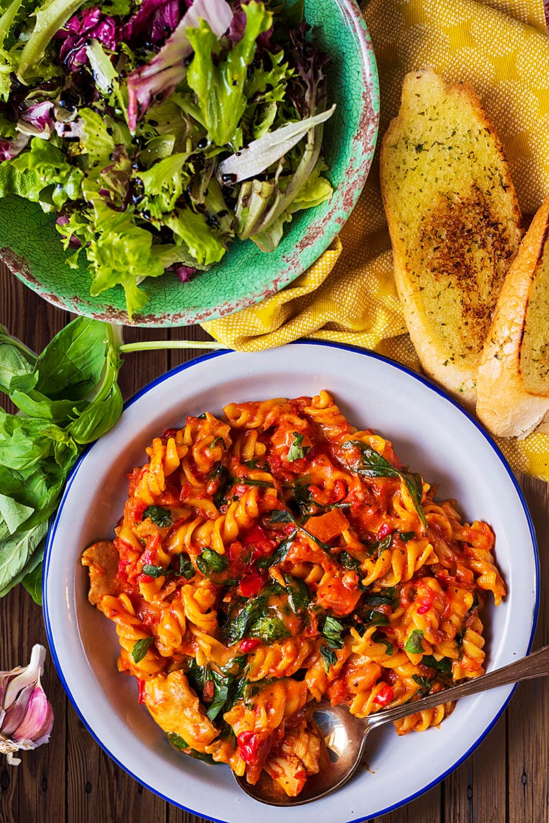 Chicken pasta on a white plate next to garlic bread and a bowl of salad.