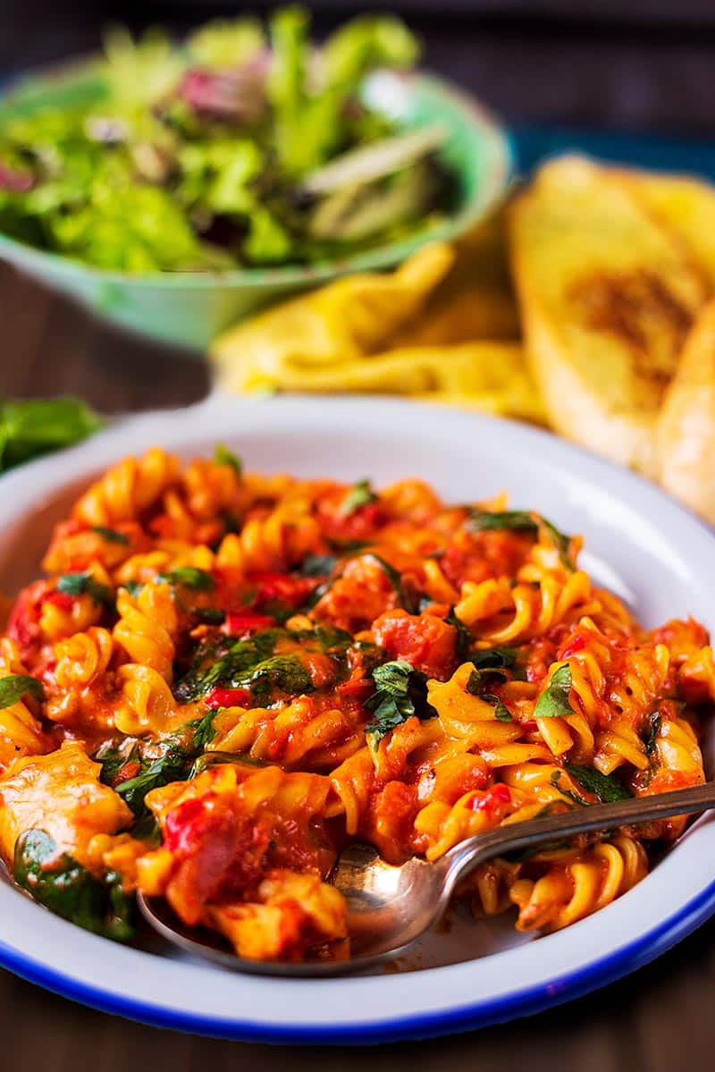 A plate of pasta in a tomato sauce with a yellow towel and bowl of salad in the background.