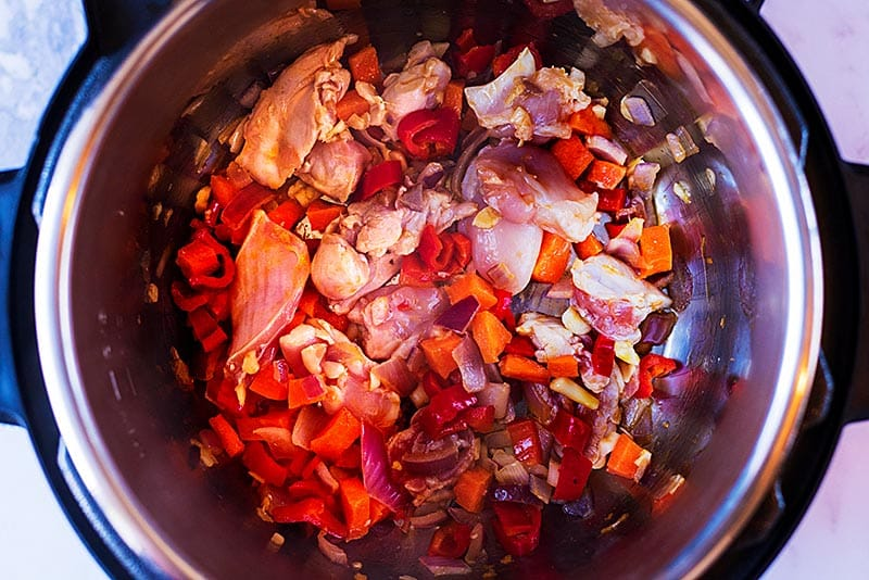 An instant pot with chopped vegetables and chunks of chicken.