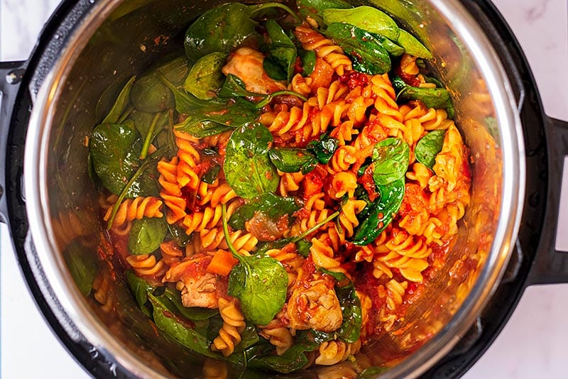 An instant pot bowl with tomato pasta and spinach.