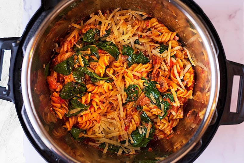 Tomato pasta with spinach and cheese in an instant pot.