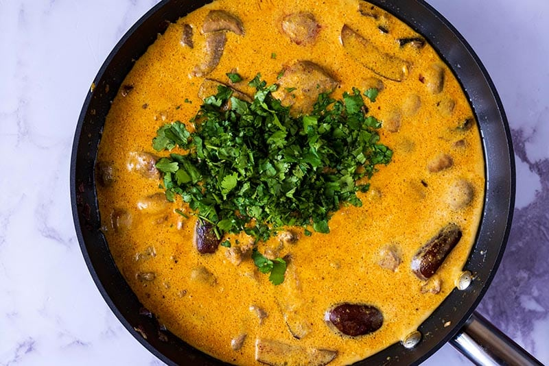 A yellow curry cooking in a pan with a large heap of cilantro in it