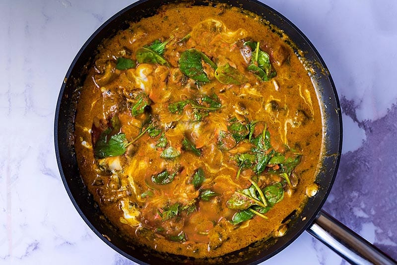 Lamb Korma in a pan with wilted spinach in it