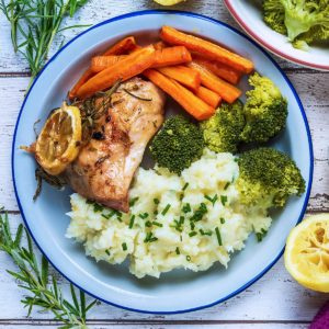 Lemon Rosemary Chicken thigh on a plate with mashed potato, carrots and broccoli