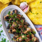 Roasted mushrooms in a long serving dish topped with chopped herbs