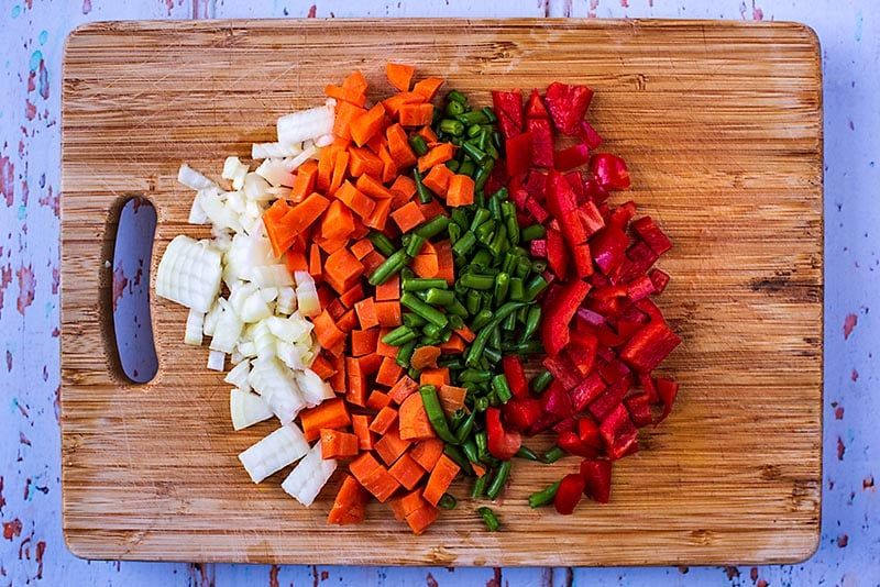 A wooden chopping board with chopped onion, carrot, green beans and red bell pepper