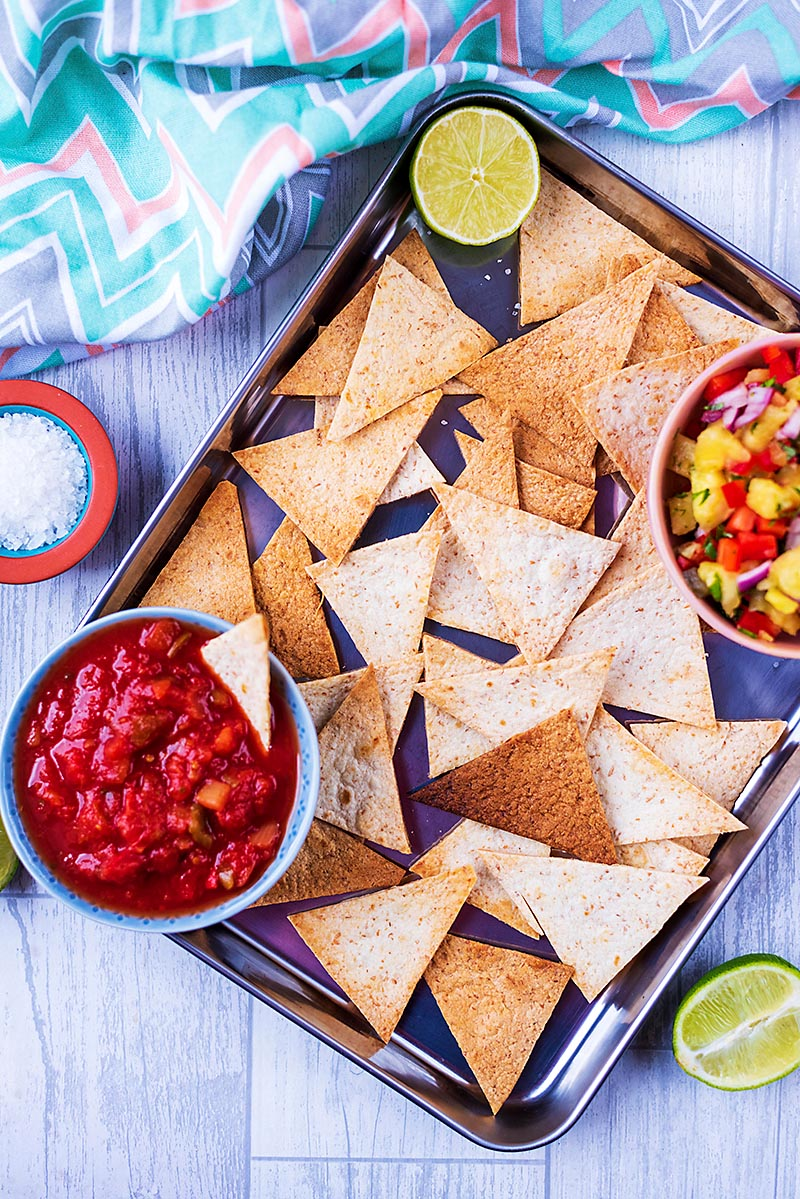 Baked Tortilla Chips on a metal tray with bowls of salsa