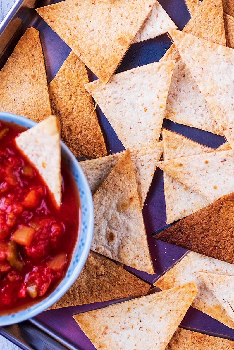 Tortilla chips next to a bowl of tomato salsa