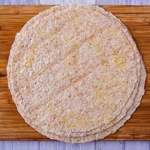 Flour tortillas spread with oil on a wooden chopping board