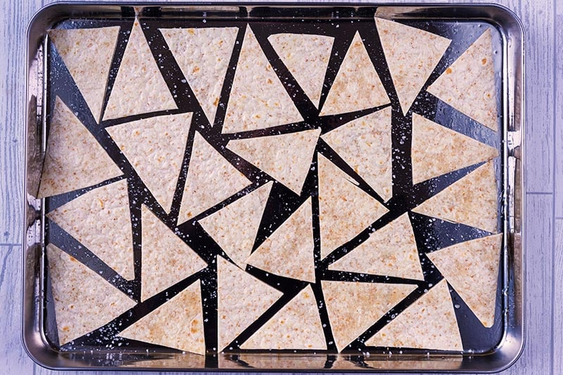 A baking sheet covered in triangles of tortilla and seasoned with salt