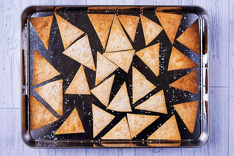 Baked tortilla chips on a baking tray