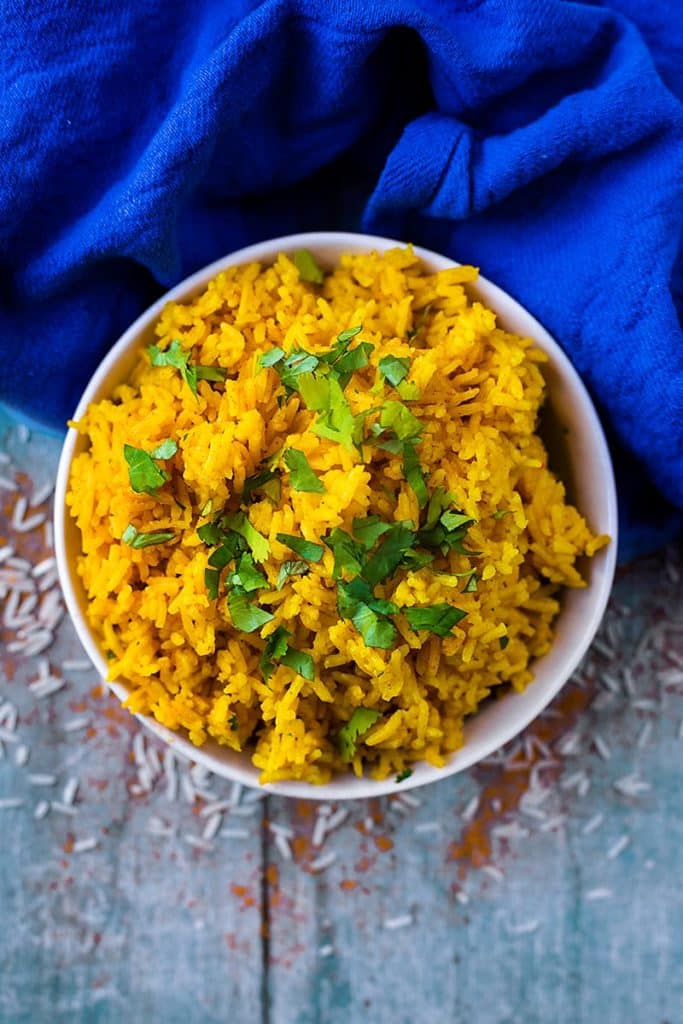 A bowl of yellow turmeric rice next to a blue towel