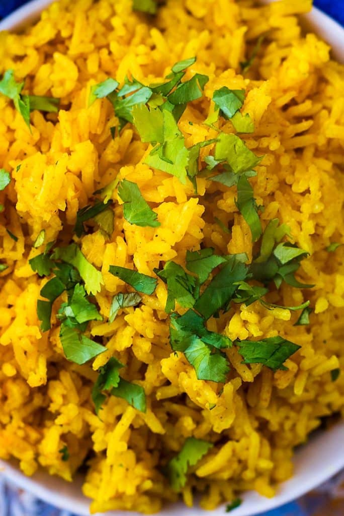 Chopped green herbs on top of bright yellow rice