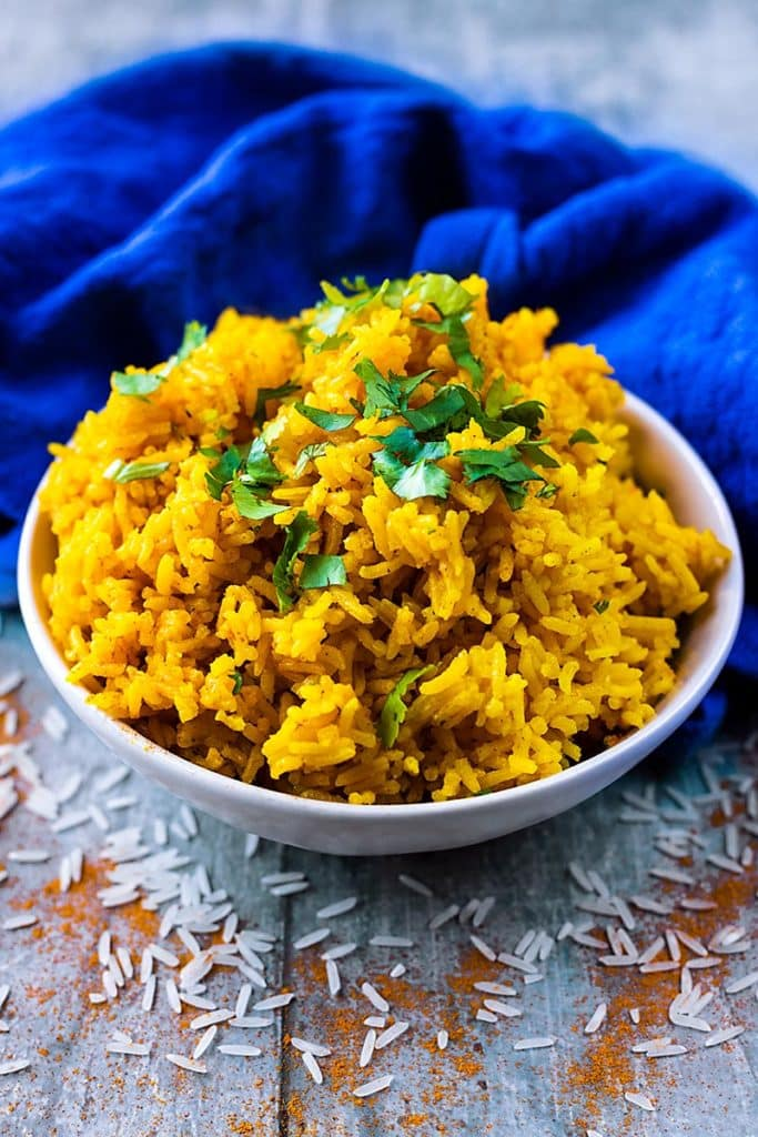 Turmeric rice topped with chopped green herbs