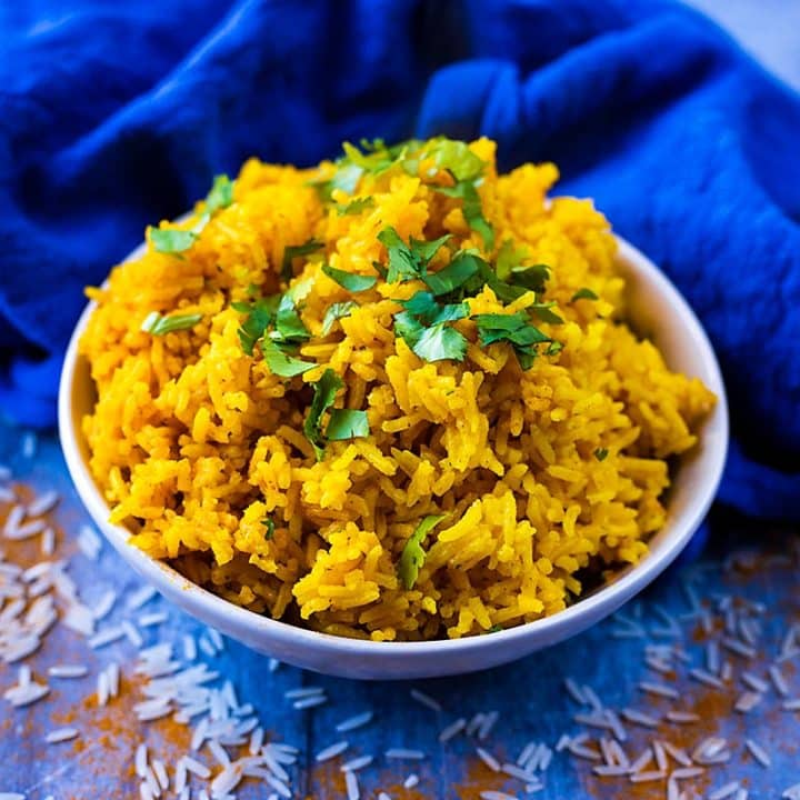 A blue bowl full of turmeric rice topped with chopped herbs
