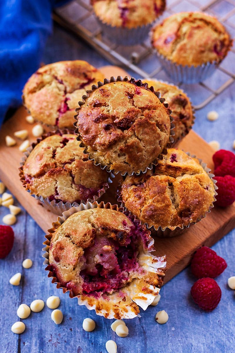 Six raspberry muffins on a board surrounded by raspberries and white chocolate chips
