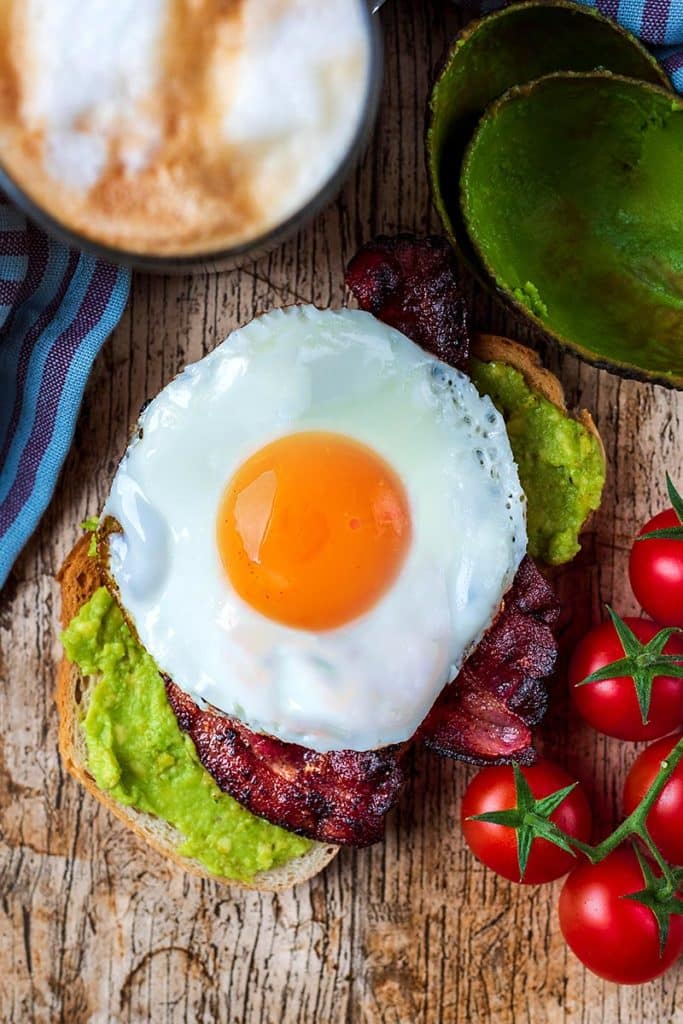 Smashed avocado on toast topped with bacon and a fried egg