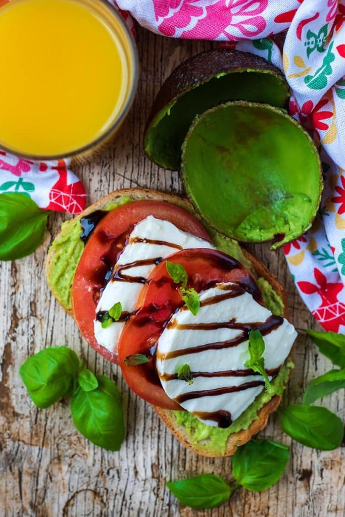 Smashed avocado on toast topped with sliced tomatoes, slices of mozzarella and balsamic vinegar