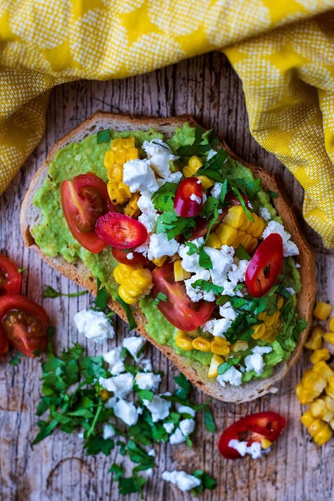 Mashed avocado on toast topped with chopped tomatoes, corn, feta cheese and cilantro
