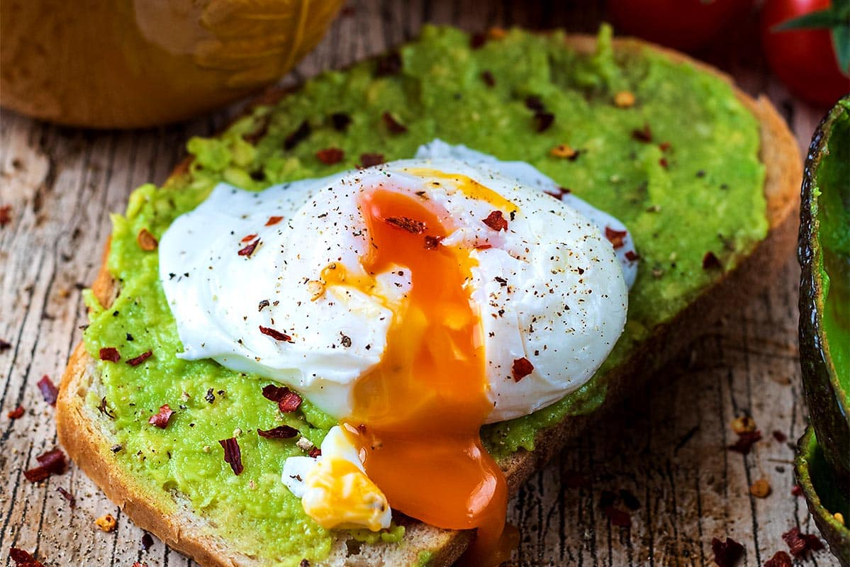 Smashed avocado on toast topped with a poached egg and chili flakes